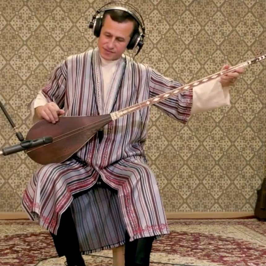 A man wearing traditional Tajik clothes plays a lute.